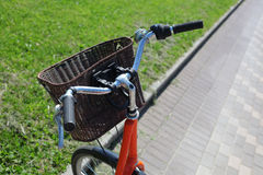 Bicycling in the park. Orange road bike with a basket at the helm.Bicycle in a park in the parking lot stock photos