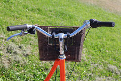 Bicycling in the park. Orange road bike with a basket at the helm.Bicycle in a park in the parking lot stock image