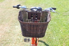 Bicycling in the park. Orange road bike with a basket at the helm. Bicycle in a park in the parking lot royalty free stock photo