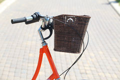 Bicycling in the park. Orange road bike with a basket at the helm.Bicycle in a park in the parking lot stock photography