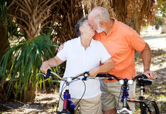 Bicycling Seniors Kiss Stock Photography
