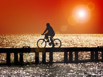 Bicycling at sunset. Silhouette of man bicycling across bridge at sunset with lens flare Stock Images