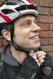 Bicyclist adjusting his helmet Royalty Free Stock Image