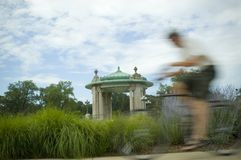 Bicyclist Blur 2. A bicyclist blurs by a pagoda in the background Stock Photo