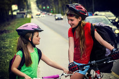 Bicyclist child ride on city bicycle path . Girls wearing helmet . Stock Photo