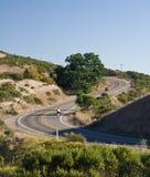 Bicyclist em uma estrada da montanha Fotografia de Stock Royalty Free