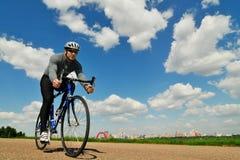 Bicyclist en un fondo del cielo Imagen de archivo libre de regalías