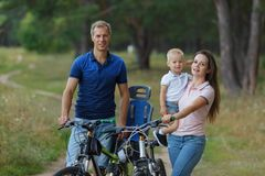Bicyclist family, leisure in pine forest. Happy parents. Couple with son walks on bikes in park, cycling royalty free stock photos