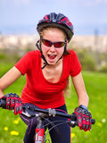 Bicyclist girl rides bicycle out city. Stock Photos