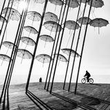 A bicyclist and a girl under the umbrellas