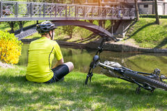 Bicyclist having rest in city park. Sunny summer hot day Royalty Free Stock Photography
