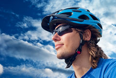 Bicyclist in helmet and sunglasses. Portrait of a young bicyclist in helmet and glasses on a sky background stock image