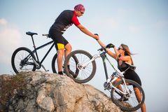 Bicyclist helping to his partner with a mountain bike Royalty Free Stock Photo