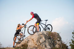 Bicyclist helping to his partner with a mountain bike Royalty Free Stock Images