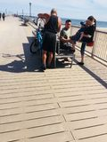 Bicyclist helps cover wound child knee band aid. There is summer season in Coney island , New York , where swimming ,hiking , fishing and playing on beach place stock photography