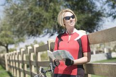 Bicyclist Holding Roadmap While Leaning On Fence. Female bicyclist holding roadmap while leaning on fence in park Royalty Free Stock Photos