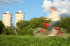 Bicyclist in motion blur against trees and houses Royalty Free Stock Photo