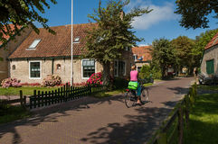 Bicyclist and old houses in Hollum village, Ameland, Netherlands Royalty Free Stock Photography