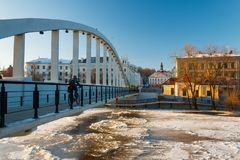 Bicyclist on the pedestrian bridge Kaarsild in the winter, Tartu, Estonia. Pedestrian bridge Kaarsild, Emajõgi river and the view on the Town Hall during royalty free stock image