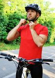 Bicyclist puts on a helmet. Outdoors Royalty Free Stock Photo