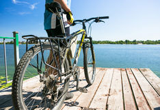 Bicyclist relax in a pear near river. Sunny summer hot day Royalty Free Stock Photo