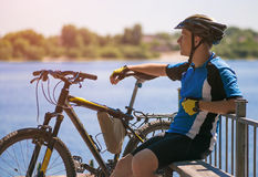 Bicyclist relax in a pear near river. Sunny summer hot day Royalty Free Stock Images
