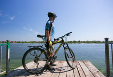 Bicyclist relax in a pear near river. Sunny summer hot day Stock Image