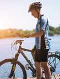 Bicyclist relax in a pear near river. Sunny summer hot day Royalty Free Stock Image