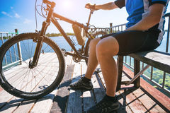 Bicyclist relax in a pear near river. Sunny summer hot day Royalty Free Stock Photography