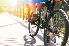 Bicyclist rides on the road in city park. Sunny summer hot day Stock Images