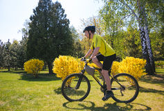 Bicyclist rides on the road in city park. Sunny summer hot day Stock Photos
