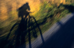 Bicyclist's Shadow Whizzing By Stock Photo