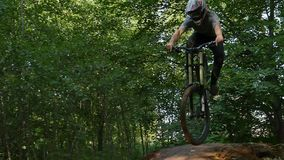 Bicyclist in safety helmet riding on mountain bike over springboard in forest. Professional bicyclist in safety helmet riding on mountain bike over springboard stock video footage