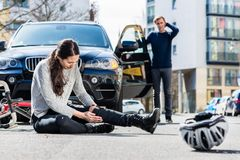 Bicyclist with serious injuries after traffic accident. Full length of a young female bicyclist fallen down on street with serious injuries after traffic stock photo