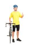 Bicyclist sorridente che propone e che dà pollice in su Fotografie Stock