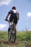 Bicyclist su un cielo della priorità bassa Immagini Stock