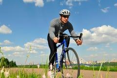 Bicyclist su una priorità bassa del cielo Fotografia Stock Libera da Diritti