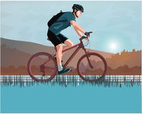 Bicyclist at sunrise. On the background of mountains in blue Royalty Free Stock Photography