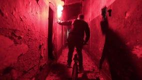 Bicyclist z czerwonym sygnałowym światłem w jego ręce jedzie nad zaniechanym budynkiem zbiory wideo