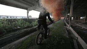Bicyclist z pomarańczowym sygnału dymem w jego ręce jedzie nad zaniechanym budynkiem zbiory