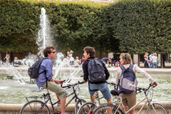 Bicyclists chat in front of fountain in Palais Royal garden in P Stock Images