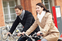 Bicyclists in a city. Happy bicyclists riding bikes in a city Stock Image