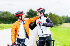 Bicyclists embrace each other in finish celebrating Stock Photo