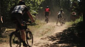 Bicyclists racing in forest taking turn on dusty road. Bicyclists in helmets and sportive clothes racing in forest taking turn on dusty road on sunny summer day stock video footage