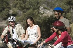 Bicyclists With Roadmap. Group of friends looking at map on cycling trip Royalty Free Stock Photography