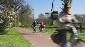 Bicyclists with windmill in The Netherlands stock video