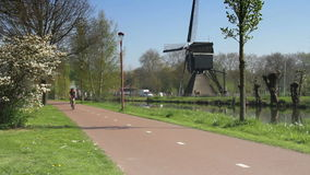 Bicyclists with windmill in The Netherlands stock footage