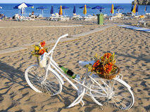 Bicykl parkujący na plaży obok parasoli Zdjęcie Stock