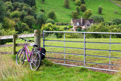 Bicyle against fence in green countryside Stock Photo