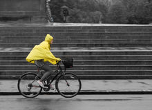 Bicyle in rain with yellow poncho. A bicyclist in the rain with a yellow poncho near Hyde Park in London in front of a monument close to the Royal Albert Hall Stock Photography